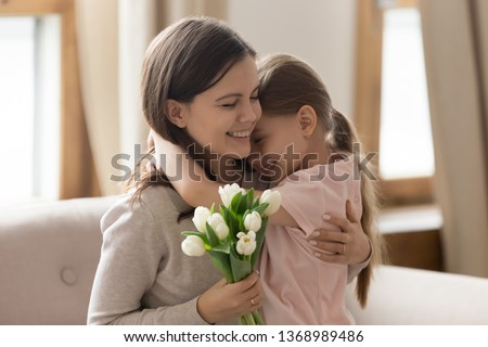 Overjoyed sisters embracing sitting on couch mother closed eyes enjoy pleasant moment adorable loving kid girl daughter congratulate on international women day make surprise white tulips concept image
