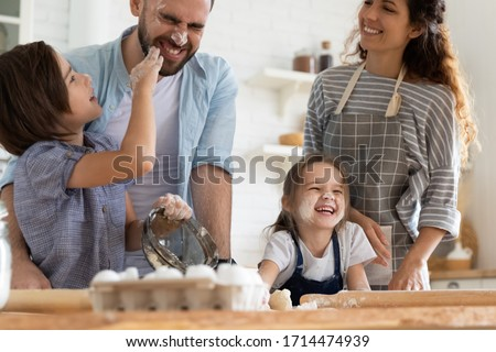 Overjoyed small children siblings spreading flour on laughing parents, enjoying cooking homemade pastry together in kitchen. Happy married couple involved in funny family activity with little kids.