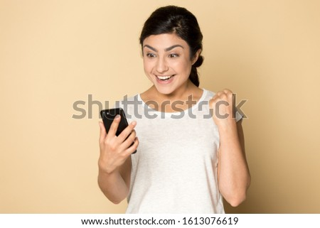 Overjoyed surprised young indian lady holding mobile phone, received good news notification, making yes gesture, celebrating online lottery win or important achievement isolated on beige background.