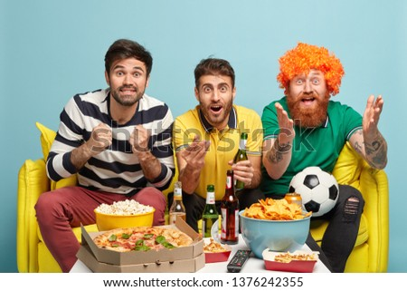 Overjoyed three best male friends being very emotional, clench fists from joy, support football team, watch game with great interest, sit on sofa, pose against blue background. Sport supporters