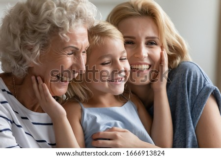 Overjoyed three generations of women hug cuddle relax at home having fun together, cute little girl play rest with young mother and senior grandmother, happy family enjoy leisure weekend indoors Stockfoto ©