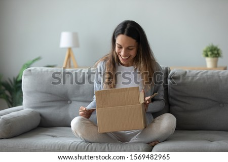 Overjoyed woman seated on sofa hold on lap small cardboard box open parcel client feels satisfied bought goods in internet, happy addressee received package from friend, quick delivery service concept