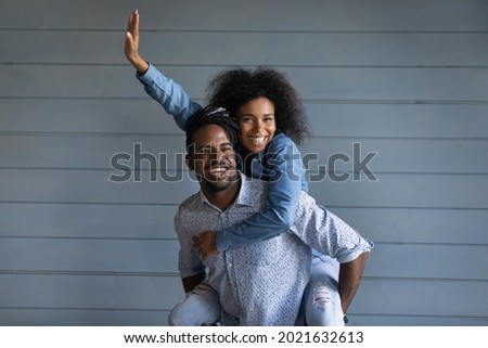 Overjoyed young African American couple renters have fun hug cuddle isolated on grey wall background. Smiling millennial ethnic woman piggyback happy biracial man show love. Rental, moving concept.