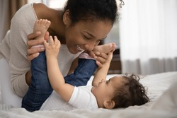 Overjoyed young African American mother relax play with smiling small biracial toddler daughter. Happy loving ethnic mom have fun enjoy motherhood with little baby girl child. Parenthood concept.
