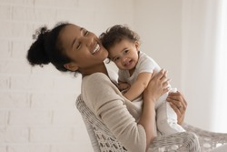 Overjoyed young african American mother sit in chair hug cuddle little newborn baby, happy biracial mom embrace small infant girl child, show love and care, enjoy maternity leave, childcare concept