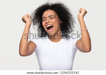 Overjoyed young african american woman screaming with joy celebrating victory win success isolated on blank grey white studio background, happy excited black girl rejoicing triumph feeling winner