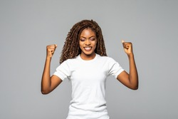 Overjoyed young african american woman screaming with joy celebrating victory win success on white background, happy excited black girl rejoicing triumph feeling winner
