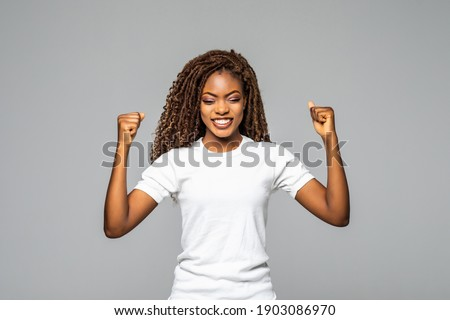 Overjoyed young african american woman screaming with joy celebrating victory win success on white background, happy excited black girl rejoicing triumph feeling winner Stock photo ©