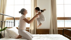 Overjoyed young Asian mom sit on bed feel playful have fun with cute little preschooler daughter, happy Vietnamese mother or nanny jump play with small biracial girl child in bedroom together