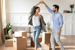 Overjoyed young Caucasian couple renters have fun excited moving in new home together. Happy man and woman tenants dance enjoy relocation day to own house. Relocation, real estate, rent concept.