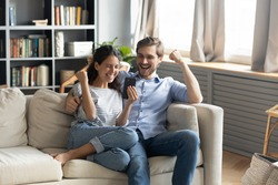 Overjoyed young Caucasian couple sit relax on couch in living room triumph winning online lottery on cellphone, happy man and woman feel excited reading good unexpected pleasant news on smartphone