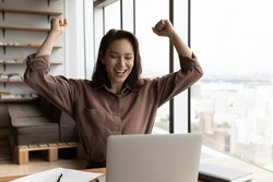 Overjoyed young Caucasian female employee look at laptop screen triumph reading good news online. Happy woman feel euphoric with amazing unexpected message or email on computer. Success concept.