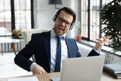 Overjoyed young Caucasian male office employee in suit wear headset listen to rock music at workplace, happy businessman in headphones relax have fun enjoy good quality audio, stress free concept
