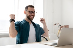 Overjoyed young Caucasian man in glasses look at laptop screen triumph win lottery online. Happy excited male employee feel euphoric get pleasant news or promotion letter on computer. Luck concept.
