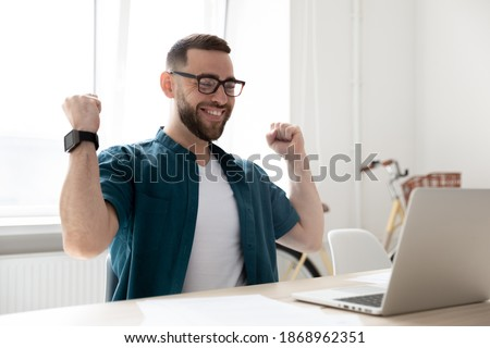 Overjoyed young Caucasian man in glasses look at laptop screen triumph win lottery online. Happy excited male employee feel euphoric get pleasant news or promotion letter on computer. Luck concept. Foto d'archivio ©