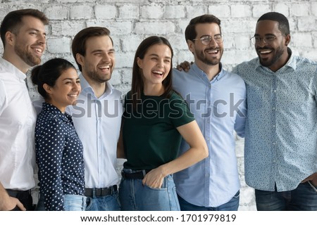 Overjoyed young diverse colleagues hug embrace posing in office together, happy multiracial businesspeople have fun laugh look at camera, show unity and motivation, teamwork concept