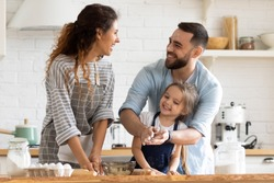 Overjoyed young family with little preschooler daughter have fun doing bakery in kitchen together, happy parents enjoy weekend with small girl child baking biscuits pastries, making pie at home