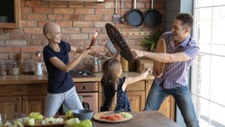 Overjoyed young family with sick cancer patient bald hairless mom and little daughter have fun engaged in playful fight in kitchen together, happy man with ill wife and small girl child play at home