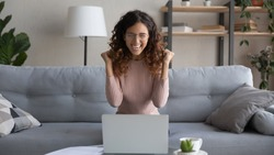 Overjoyed young female in glasses look at laptop screen feel euphoric with online lottery win or success, excited woman in eyewear triumph read pleasant good news in email on computer, luck concept