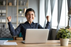 Overjoyed young Indian woman sit at desk in living room feel euphoric win lottery online on laptop, excited millennial ethnic girl triumph receive read pleasant approval email on computer