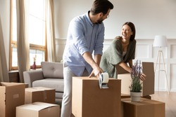 Overjoyed young married couple preparing personal stuff for removal day. Happy husband using adhesive scotch, preparing belongings for transportation, while smiling wife put things in carton box.