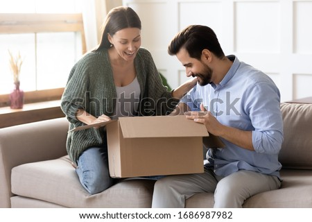 Overjoyed young married couple sitting on sofa, unpacking cardboard box at home. Happy family spouses clients satisfied with purchase in internet store or fast international shipping delivery.
