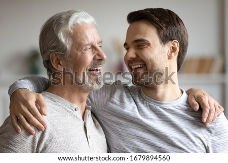 Overjoyed young millennial man embrace mature dad have fun talk and laugh at home, happy elderly father hug grown-up adult son enjoy family weekend reunion, show family love and care
