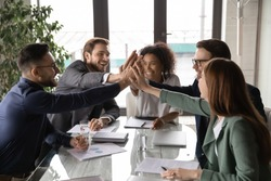 Overjoyed young mixed race business people sitting at table, joining hands in air, showing group unity, celebrating successful teamwork or professional achievement, raising team spirit at meeting.