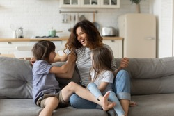 Overjoyed young mother having fun with two kids at home, laughing happy mum, adorable little daughter and son playing funny active game, tickling, sitting on cozy couch in living room