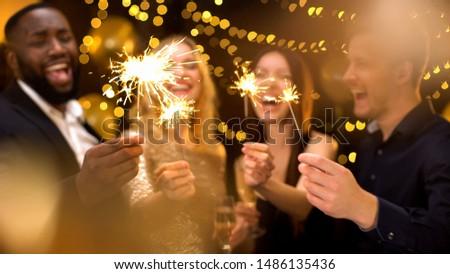 Overjoyed young people celebrating new year, holding bengal lights, having fun