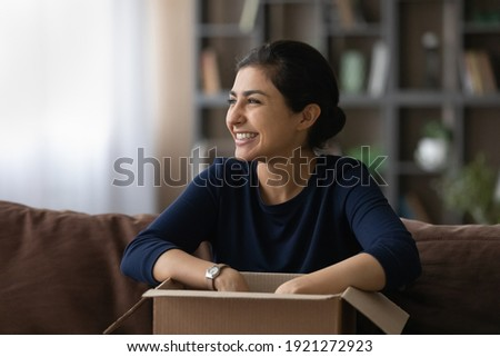 Overjoyed young 20s Indian woman feel excited with good quality order shopping online from home. Smiling millennial ethnic female buyer unbox unpack parcel buying on web. Delivery, shipping concept. Photo stock ©