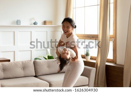 Overjoyed young Vietnamese mother have fun enjoy weekend with cute little biracial daughter at home, happy Asian mom or nanny play with small girl child in living room involved in activity together