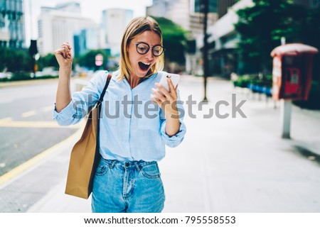 Overjoyed young woman reading message from friend on mobile expressing happiness about great news,emotional female in eyeglasses excited with winning discount for shopping while walking in downtown