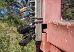 Overkill with six different padlock locks securing a metal gate from being opened
