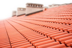 Overlapping rows of red tiles roof with chimneys in Poland, ridge tiling material regular pattern background in horizontal orientation, nobody.