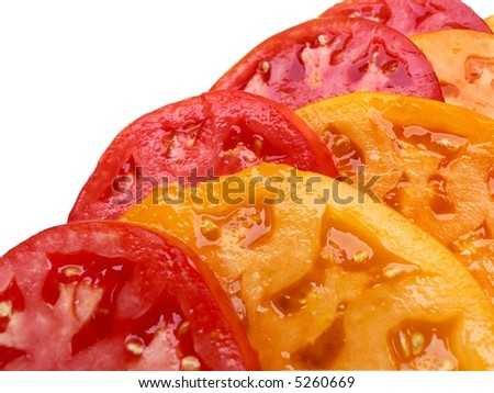 Overlapping slices of red and yellow tomatoes, isolated on white background.