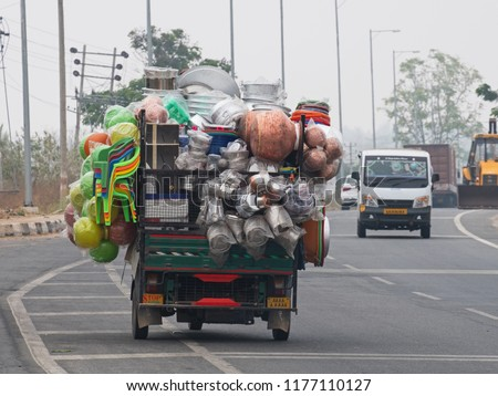 Overloaded commercial vehicle carrying household goods on a main highway south of Mysore, India. Excessive loads are commonplace on South Asian roads