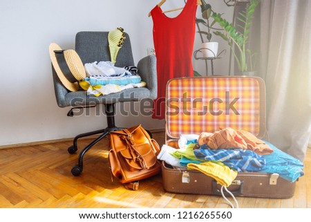 overloaded valise with clothes. prepared garment on chair. travel concept