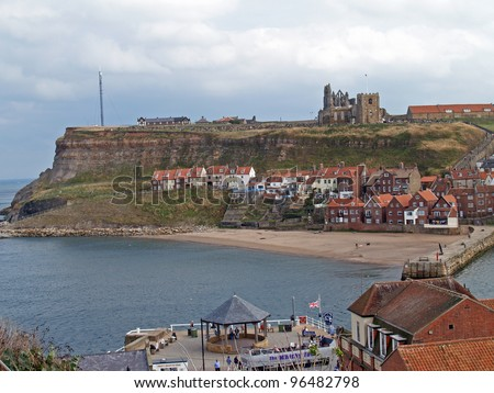 Overlook of the East Cliff of Whitby, North Yorkshire, England showing old cottages, church, and abbey ruins in the background - stock photo