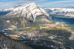 Overlook view Town of Banff, Cascade Mountain and surrounding snow-covered Canadian Rocky Mountains in early winter time. Banff National Park, Alberta, Canada.