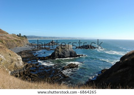 overlooking lava rocks deposited on the oregon coast from high above on cliff as the cliff swoops around