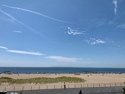 Overlooking the Coney Island boardwalk from an elevated point. There is the wood boardwalk, the beach, ocean, sand, waves, docks, and lots of large buildings in the cityscape.