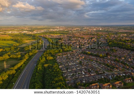 Overlooking typical British housing estates with stunning hills and moorland in the background. Beautiful green fields are separated by an empty, quiet motorway, lit by the golden sunset light.  #1420763051