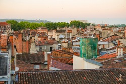 Overlooking view at dawn over the tiled roofs of old traditional, Southern townhouses in Carmes, an historic neighborhood in the city centre of Toulouse, France, with the hill of Pech-David afar
