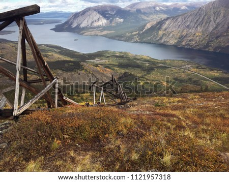 Overlooking Windy Arm on Tagish Lake with its beautiful fall Colours. The remnants of silver mine's tram way dating back to 1905 litter the side of Montana Mountain. Carcross, Yukon, Canada.