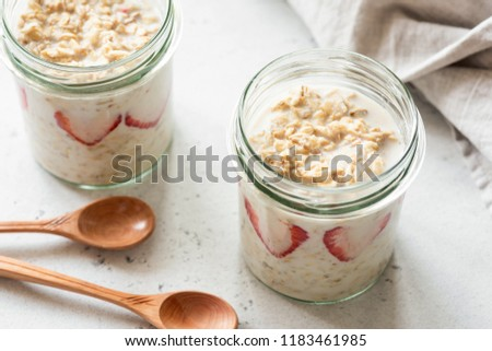 Overnight oats or oatmeal in a jar on concrete background. Healthy eating, healthy lifestyle concept