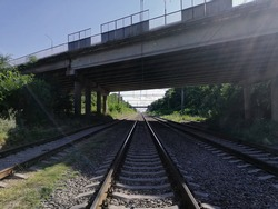 Overpass over railroad tracks against the sun and blue clear sky