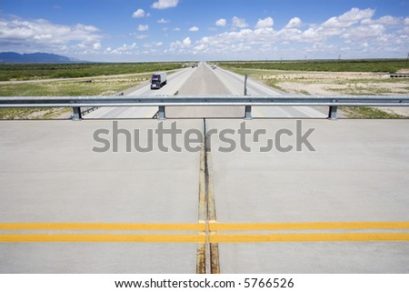 Overpass with highway below with tractor trailer truck.