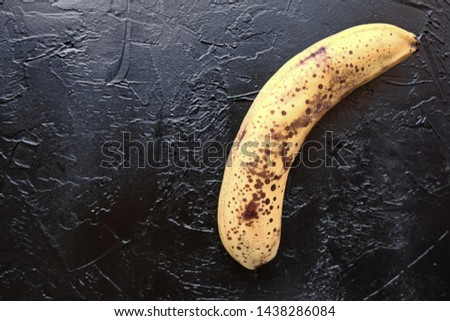 Overripe banana with dark spots on the skin on  blac background .Ugly fruit. Buying imperfect products is a way to deal with food waste. Horizontal. #1438286084