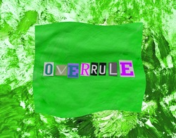 Overrule word from paper magazins letters on green distorted frame and chaotic paint strokes. Grunge textured background